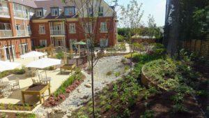 Pohled z horní části zahrady na retenční nádrž a přilehlou terasu domu s pečovatelskou službou.