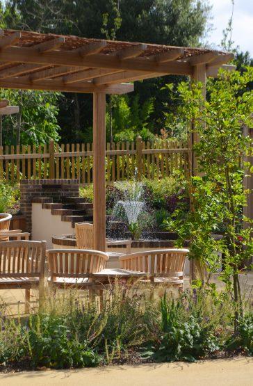 Pohled skrz pergolu s jídelním stolem na vodní kaskádu s fontánou.